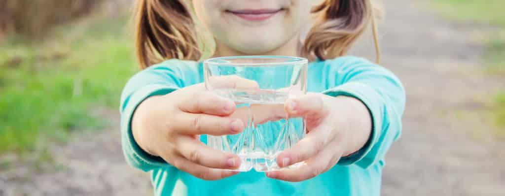 Verre d'eau tendu par une petite fille.