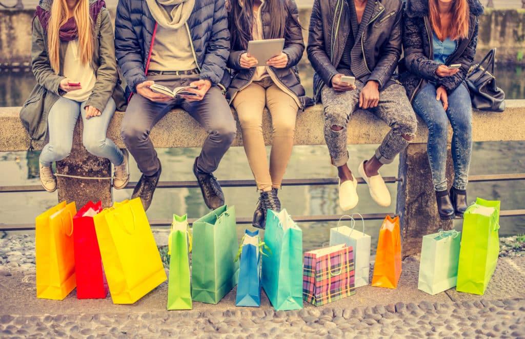 Des jeunes assis avec des sacs de shopping en Rhône-Alpes.