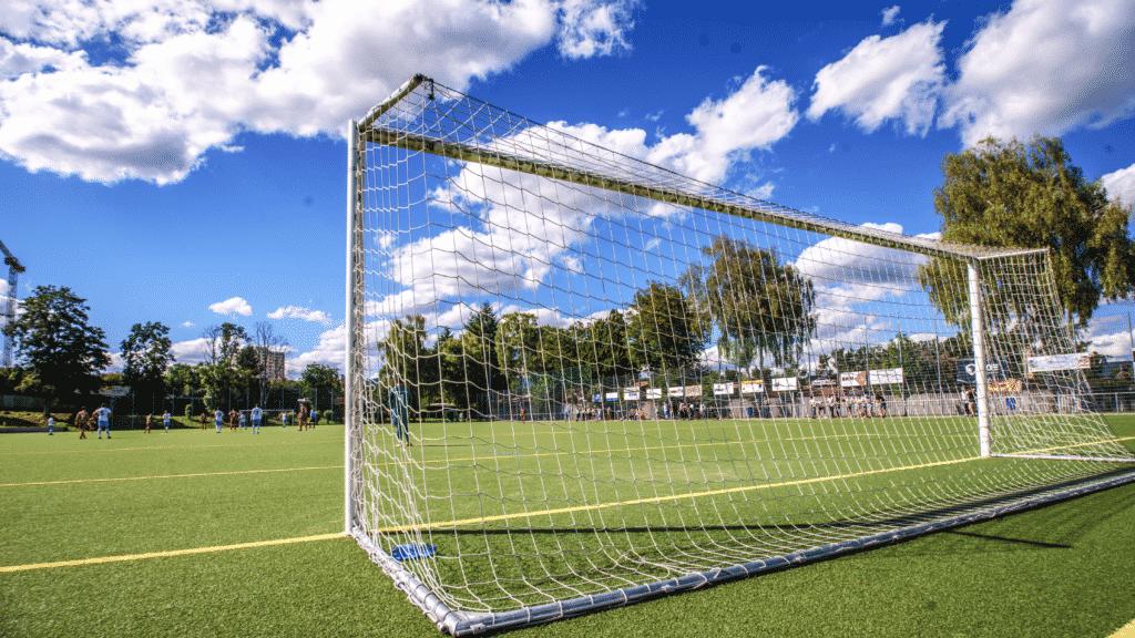 Stade de foot avec en premier plan un but.
