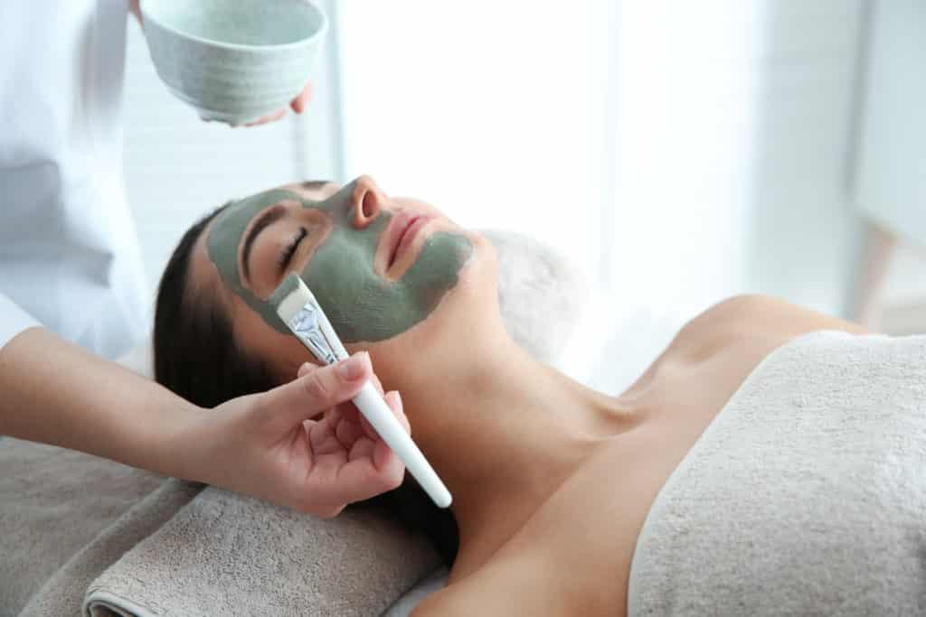 Vue sur une femme entrain de se faire faire un soin du visage.