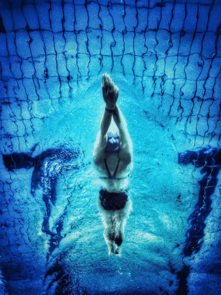 Nageuse dans une piscine entrain de nager le dos.