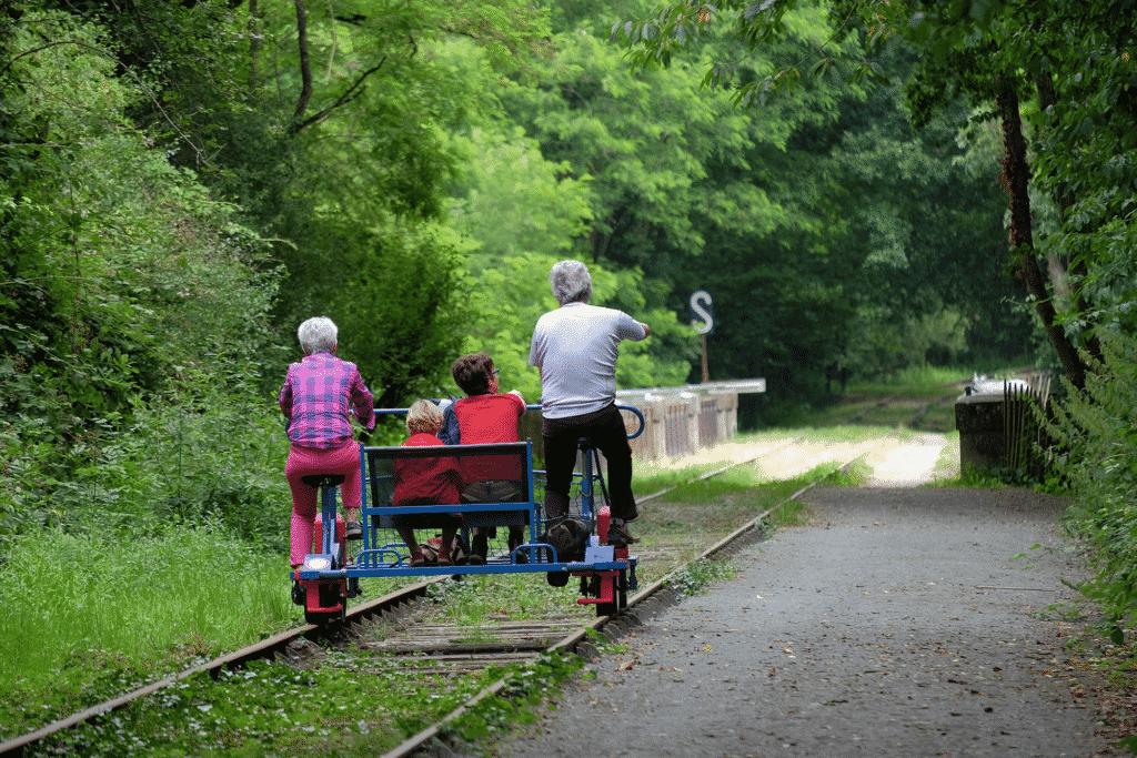 Vue sur un couple et ses enfants faisant du vélo rail.