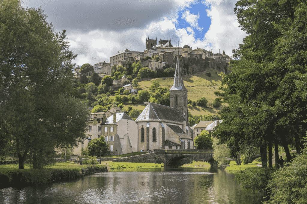 Vue sur un plan d'eau avec une église, et en partie haute la ville de Saint Flour.