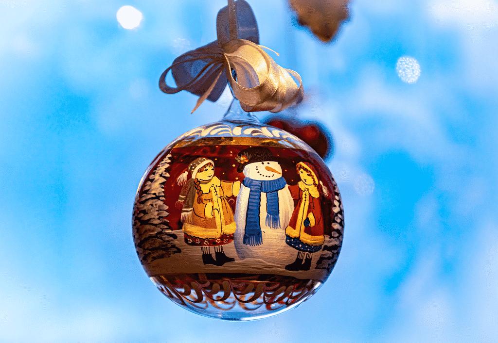 Boule de noël avec deux filles et un bonhomme de neige.