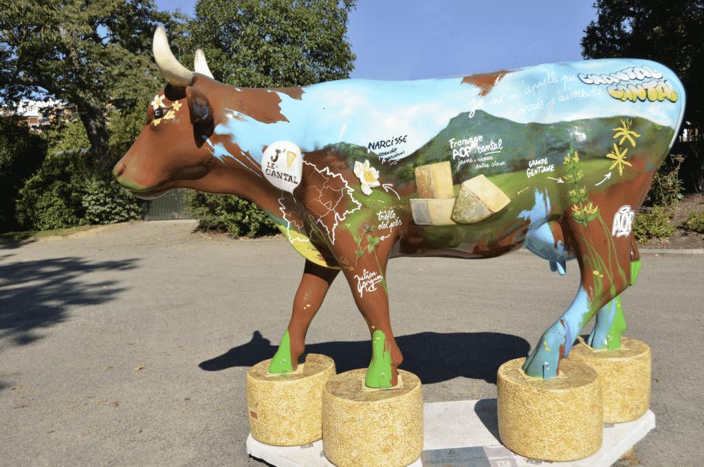 Vue sur une statue de vache peint avec des peintures à l'éffigie du Cantal.