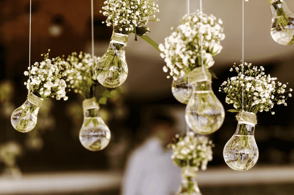 Des fleurs dans des ampoules suspendue au plafond par un fleuriste.