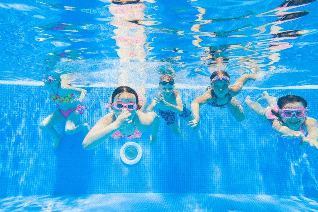 Vue sur des enfants dans une piscine qu'un pisciniste a installé.