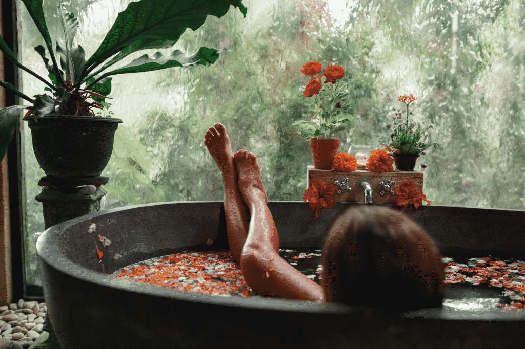 Vue sur une personne dans une baignore spa avec des pétales de fleurs.