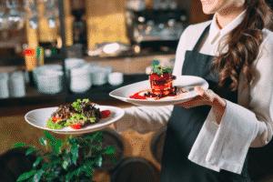 Vue sur une serveuse entrain de servir deux plats dans un restaurant.