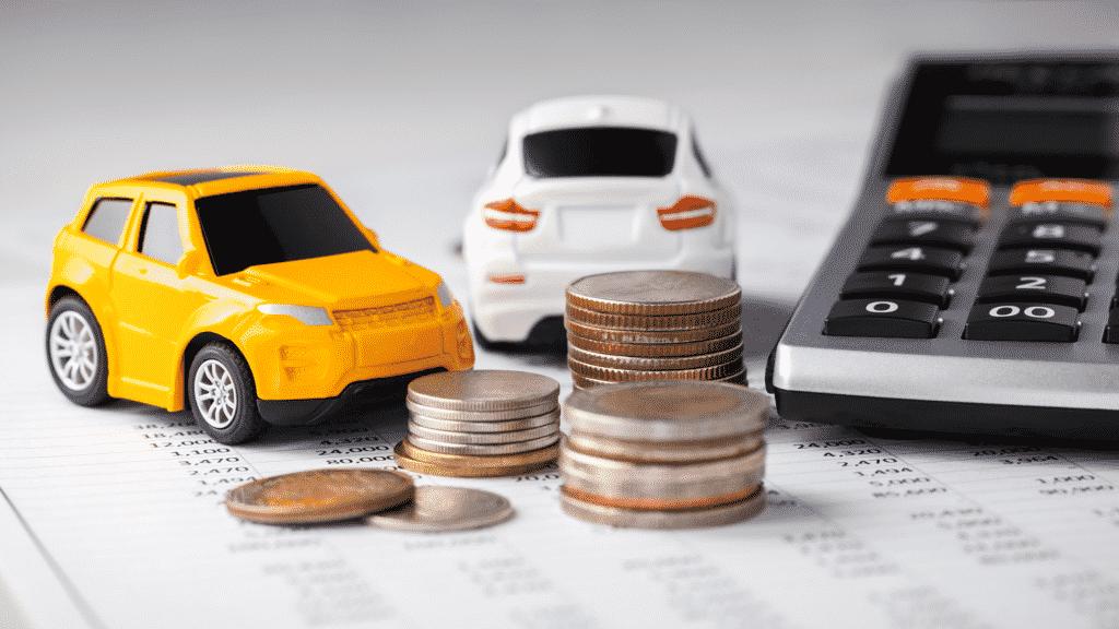 Vue sur des petites voitures, de la monnaie, une calculatrice pour symboliser l'assurance voiture.