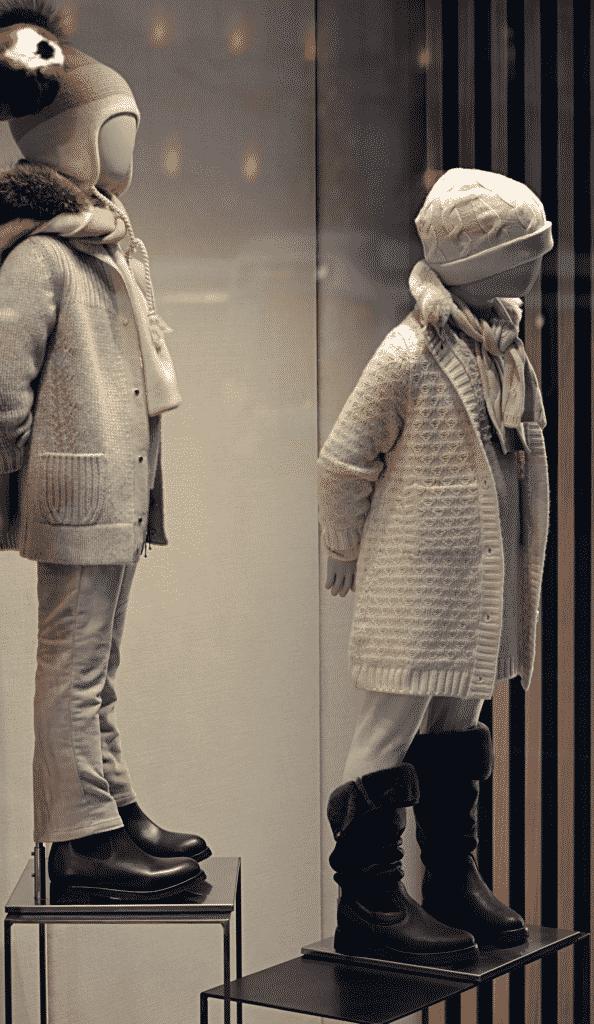 Vue sur deux mannequins en vitrine pour présenter une collection de Prêt à porter pour enfant.