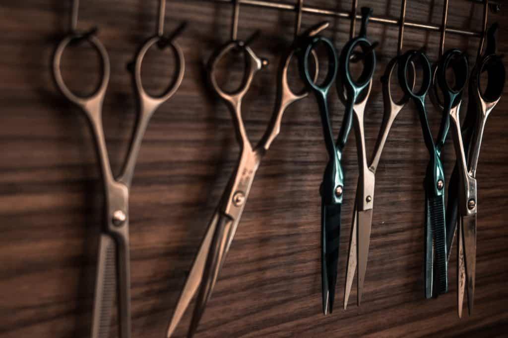 histoire de la coiffure avec des ciseaux accrochés au mur chez un coiffeur.
