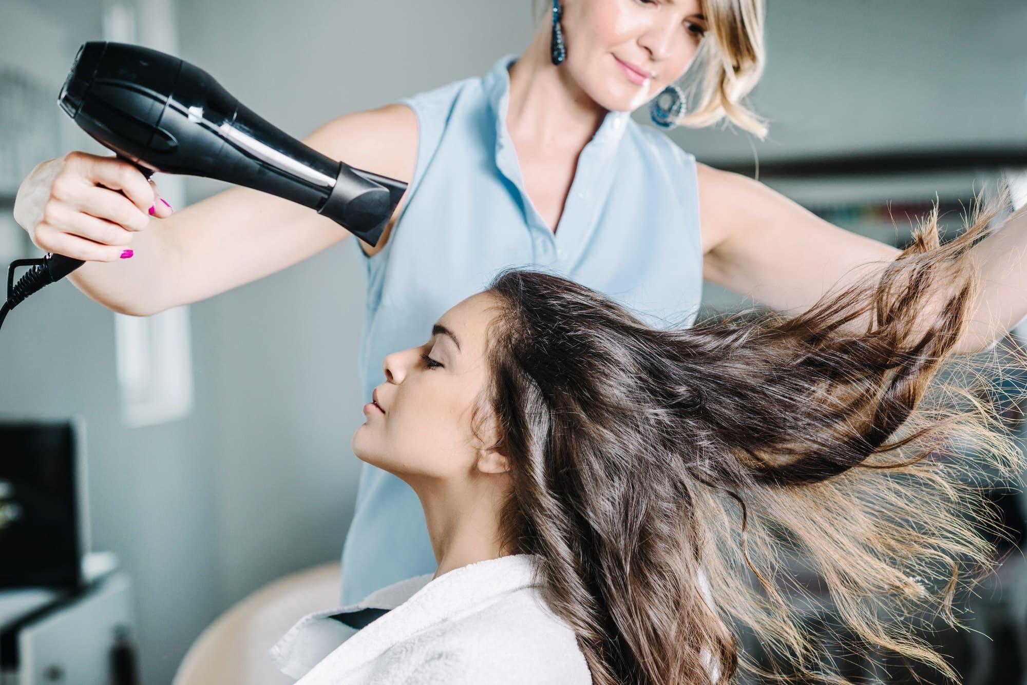 Une femme entrain de se faire sécher les cheveux par une coiffeuse.