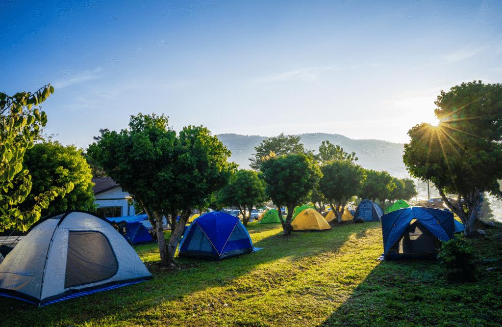 Vue sur un camping avec ses tentes au levée du jour.