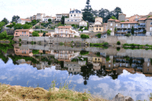 Vue sur le village de Saint Just Saint Rampar qui reflette dans la rivière.t