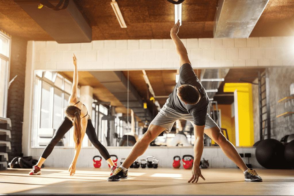 Vue sur deux personnes entrain de faire du sport en salle.