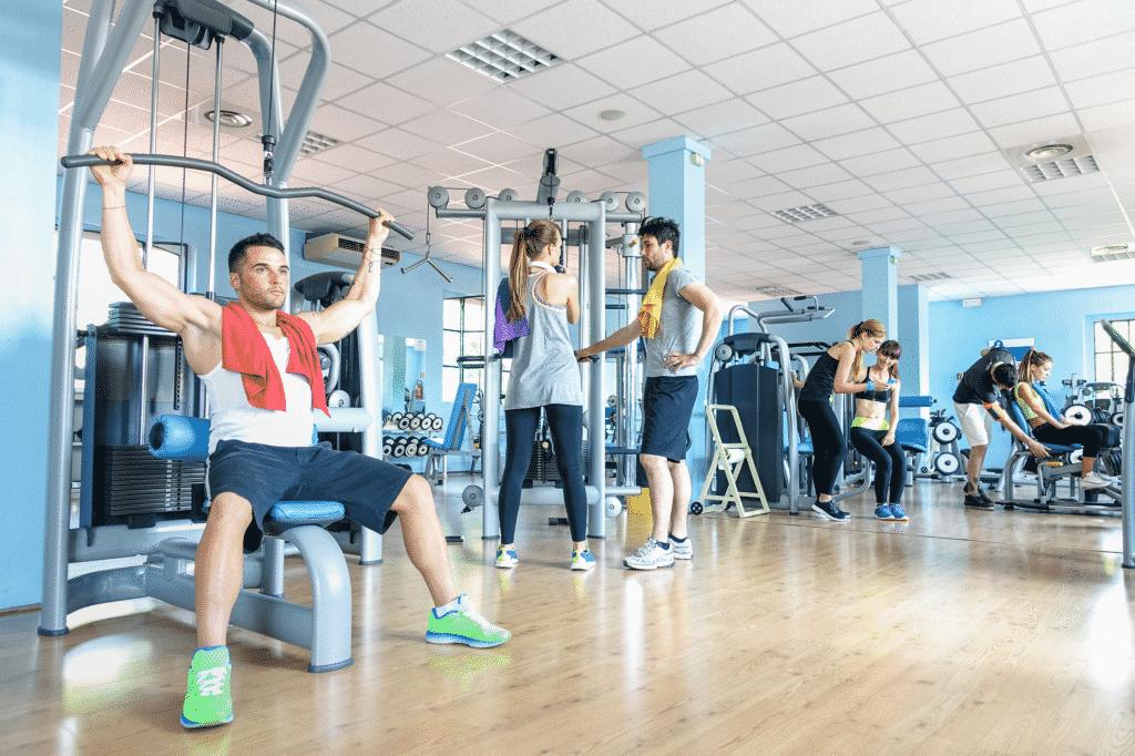 Vue sur l'intérieur d'une salle de sport avec des personnes entrain de faire de l'entretien musculaire.