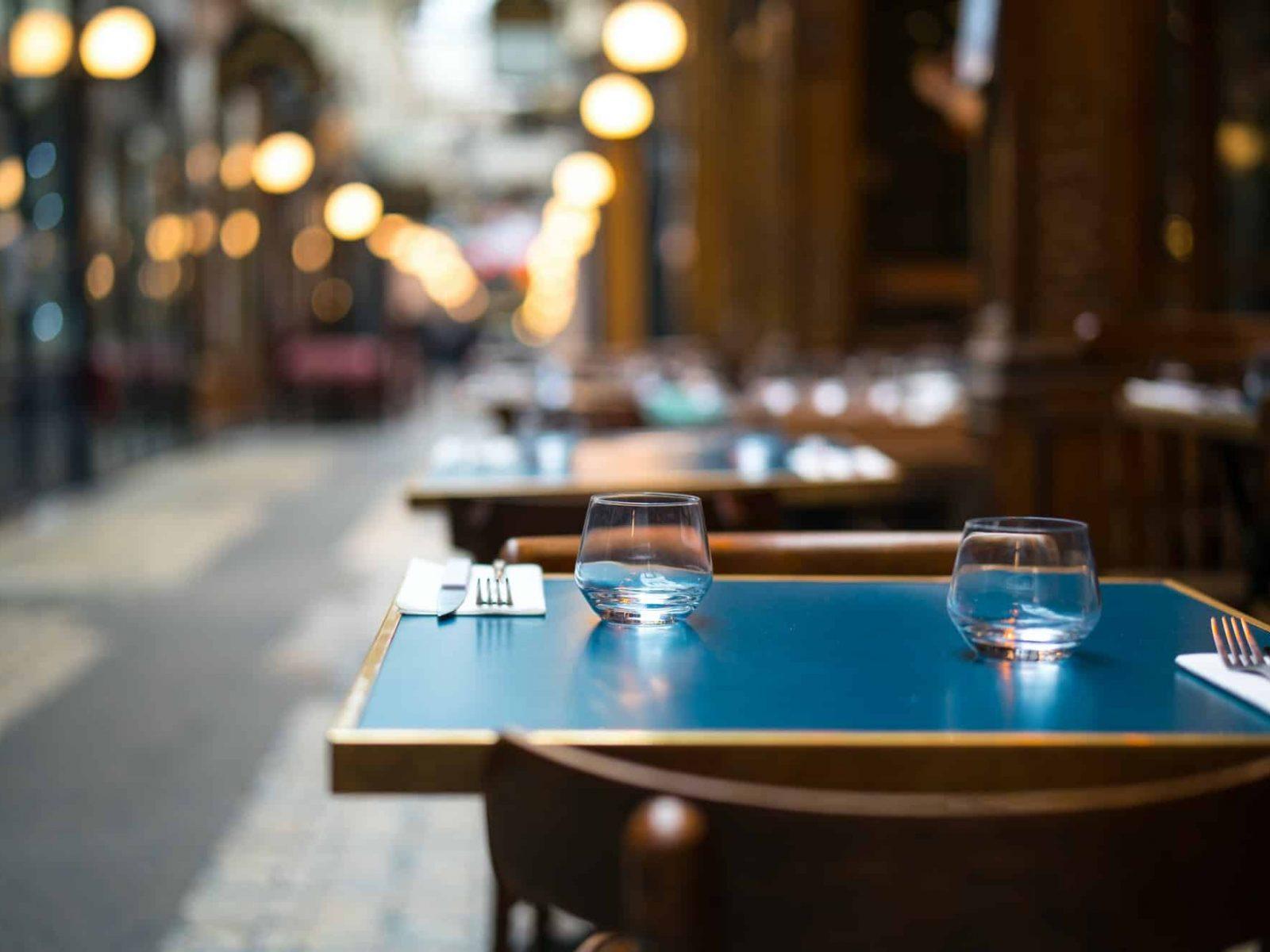 Vue sur une table dressée d'un restaurant en terrasse dans la rue.